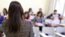 Pessoa de costas para alunos em imagem desfocada