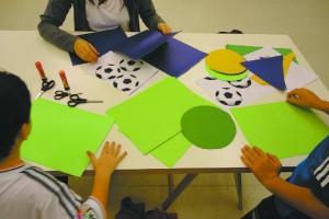 Detalhe de crianças sentadas à mesa na atividade Histórias da Arte para crianças: entre livros e obras, no MAC